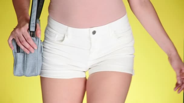 Girl in denim shorts with fashion accessories. denim reticule. Summer fresh style. colored yellow background