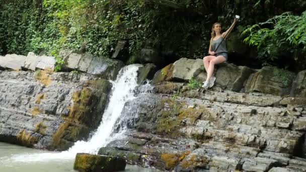 girl blogger is leading a report sitting on a rock by the waterfall. The picturesque nature of a beautiful waterfall and an emerald of a freshwater lake in the forest environment of wild jungles. 4k