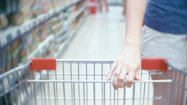A woman in a supermarket is passing by the basket past the counters. 4k, close-up, a woman in white shorts walks around the supermarket.