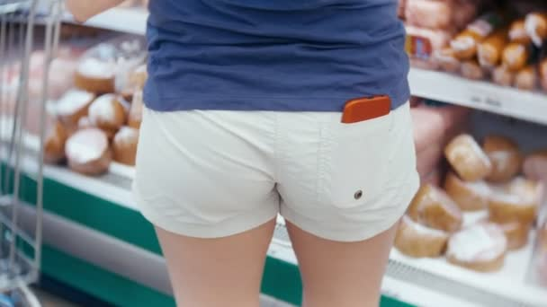 A woman in a supermarket is passing by the basket past the counters. 4k, close-up, a woman in white shorts and a red phone in her pocket walks around the supermarket.