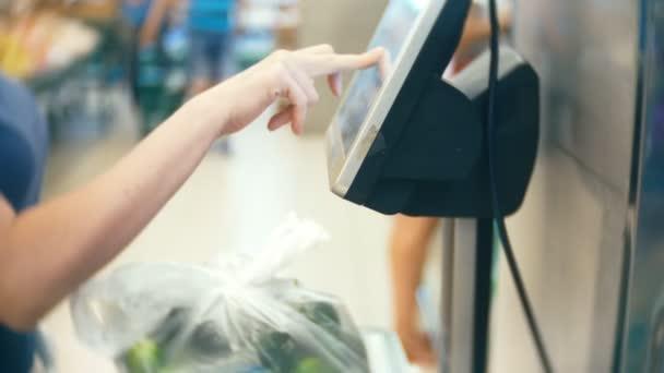 Žena v supermarketu nákup zeleniny. okurky a rajčata, váží na vahách. samoobslužné služby. 4k