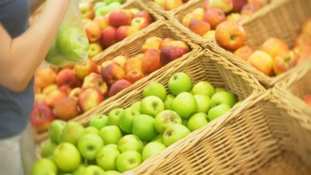 mladá žena výběr apple na ovoce zeleniny supermarketu tržiště. 4k