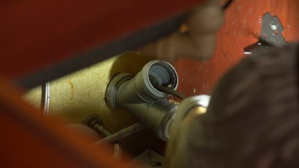 Instalatér potrubí opravy v domě. Detail. Instalatér čistí trubky s vybavením. 4k, pomalý pohyb