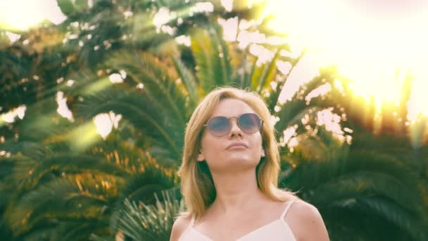 Beautiful stylish blond woman in sunglasses , walking along a palm tree path. The palm is reflected in the glasses. 4K slow motion.