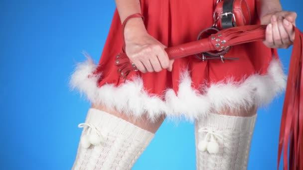 verführerische Santa Girl mit Sex-Spielzeug in verführerischen Posen. auf einem blauen Hintergrund. eine Nahaufnahme. Slow-Motion. 4k