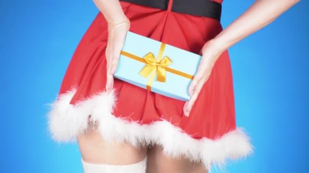 Weihnachtsferien. junge attraktive Frau im Schneemädchenkostüm mit Geschenk, die auf blauem Hintergrund tanzt. Nahaufnahme, Zeitlupe, 4k