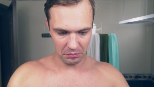 legrační pohledný chlap oholí vousy s elektrický holicí strojek v koupelně a zpívá písně před zrcadlem. 4k