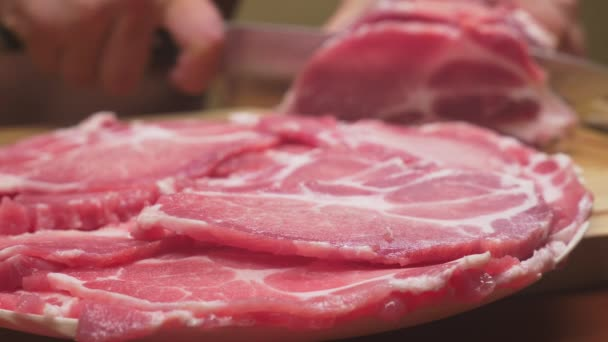 Ein Mann schneidet in Zeitlupe rohes Fleisch mit dem Messer. 4k, Nahaufnahme