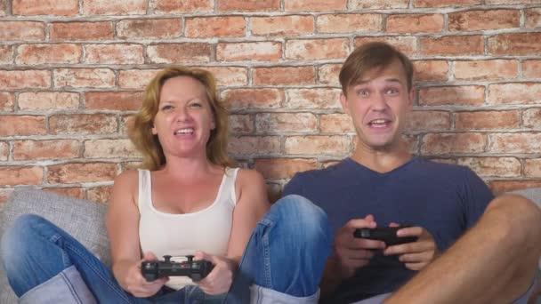 érzelmi férfi és nő játék joystick a konzol, ők versenyeznek, és hogy őrült vicces arcok. 4k, lassú mozgás
