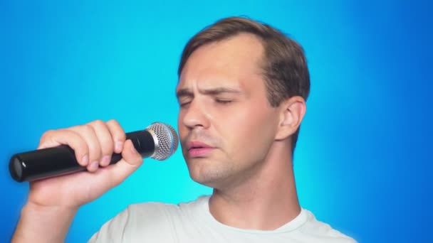 a crazy funny young man sings songs into a microphone. color background, close-up. 4k, slow motion