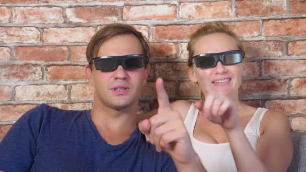 Közelről. egy fiatal pár 3D-s szemüveg, ül a díványon, a nappaliban, a sok érzelem, nézni a filmet. 4k, lassú mozgás.