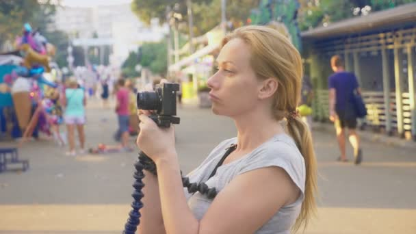 a professional photographer, takes pictures in an amusement park, a woman presses a button of a gadget among a flowering garden. 4k, slow motion, steadicam shooting