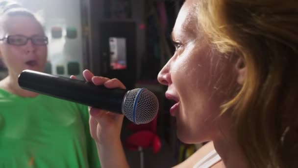 Photo Close up. a woman screaming to a microphone. a woman sings karaoke into a microphone in a home setting. 4k, slow motion.