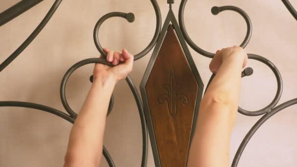 Frauenhände klammern sich an den geschmiedeten Kopf des Bettes. schmiedete Betten, Details. 4k, Zeitlupe.