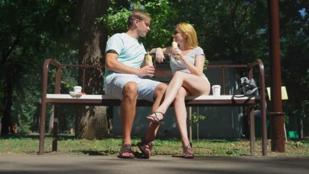 glückliches Paar, das Hotdogs isst und sich im Stadtpark auf einer Bank vergnügt. 4k, Zeitlupe.