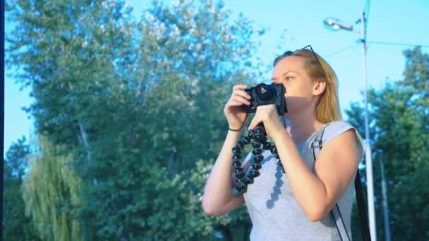 egy profi fotós képei egy vidámparkban, egy nő egy gomb-ból egy szerkentyű prések között egy virágzó kert. 4k, lassú mozgás, lövés Steadicamnél