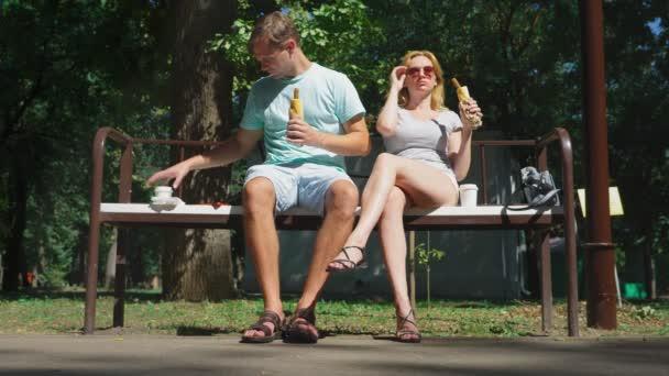 Šťastný pár jíst párky baví v městském parku na lavičce. 4k, pomalý pohyb.