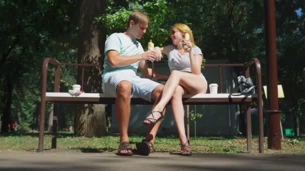 Glückliches Paar Hotdogs Spaß in einen Park auf einer Bank zu essen. 4k, Slow-motion.