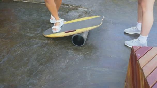 női lábak közelről. nyári napsütésben. A nők a fedélzeten balance Board. Rocker-roller táblák. ovális fából készült fedélzet balance Board. Roller balance Board. 4k, lassú mozgás