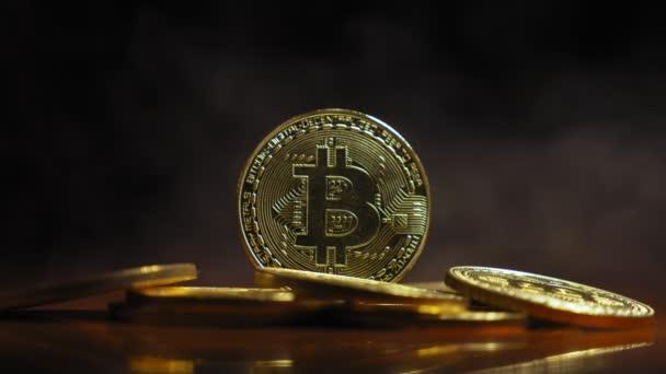 zlaté mince, bitkoyny na pozadí kouřovou clonu ve světle safitov. detail. Šifrovací měna. Virtuální měna, 4k