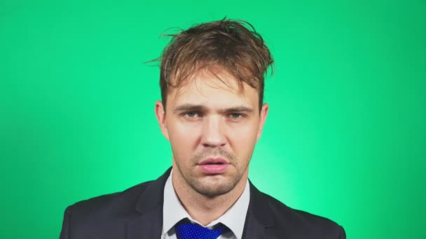 sleepy, disheveled young man in a suit and tie, yawns and looks into the camera. 4k, green background, slow motion. emotions