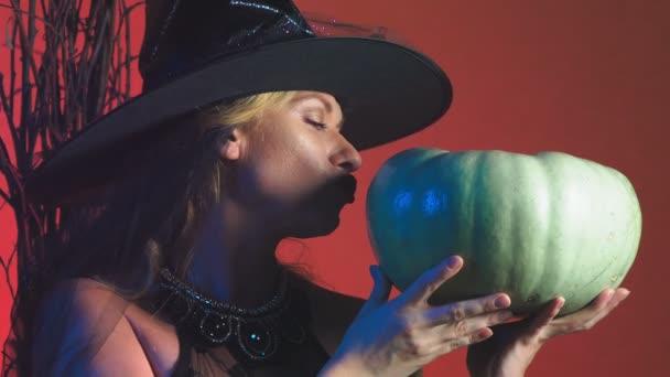schöne junge sexy Frau in einem schwarzen Hexenkostüm und Hut, mit einem Kürbis in ihren Händen. Textfreiraum. 4k, Slow-motion