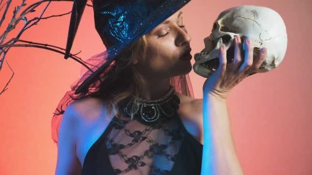 schöne junge sexy Frau in einem schwarzen Hexenkostüm und Hut mit einem Besen und einem Totenkopf in den Händen. Textfreiraum. 4k, Slow-motion