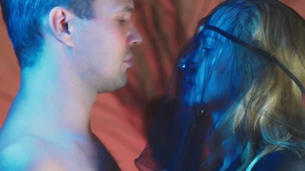 4k, Zeitlupe, Halloween. Eine Frau im Kostüm einer schrecklichen Hexe Küsse mit einer schönen nackten Mann, der Begriff der Hexerei und einen magischen Bann. close-up