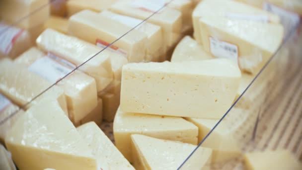 Ukázka s nasekané kousky sýra, pojem supermarket, potraviny, mléčné výrobky. 4k, detail