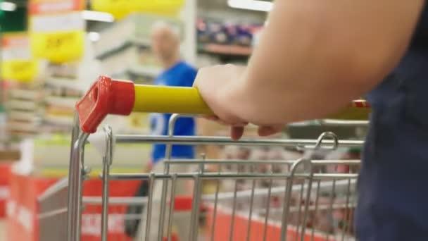 Žena v supermarketu je kolem koše za čítače. 4k, detail, ženy chodí kolem supermarketu.