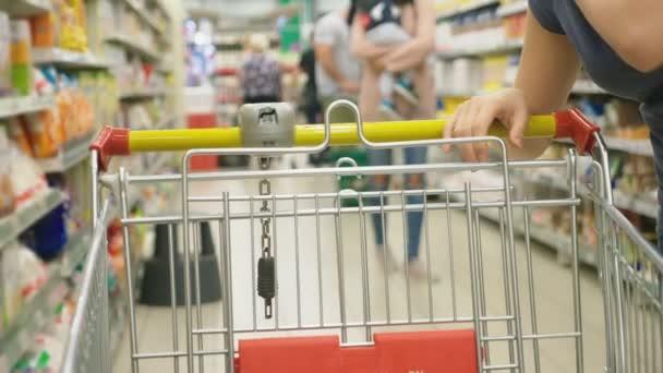 Egy nő, egy szupermarketben elhaladó a kosár múlt a számlálókat. 4k, közeli, egy nő sétál körül a szupermarketben.
