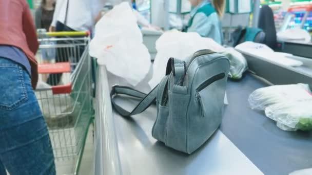 pokladní v supermarketu, Žena nakupuje potraviny na pokladně v supermarketu. 4k, detail