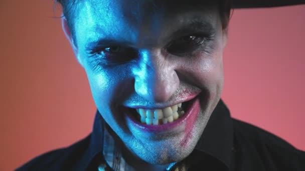 ein junger Mann in einem Zombie Halloweenkostüm, schauen Sie sich die Kamera und das Lächeln bedrohlich. 4k, Slow-motion.