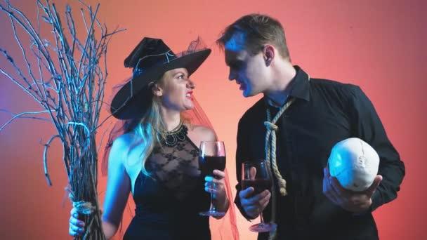 ein schönes Paar, ein Mann und eine Frau in Hexe und Zombie Kostüme Halloween, 4k, langsamen schießen, halten Gläser Wein und einem Totenkopf. Herzlichen Glückwunsch zu den Urlaub