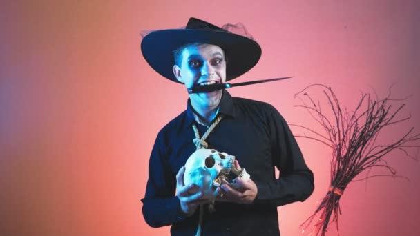 ein junger Mann in einem Zombie-Kostüm für Halloween, mit einem Schädel in seinen Händen. 4k, Slow-Motion. close-up