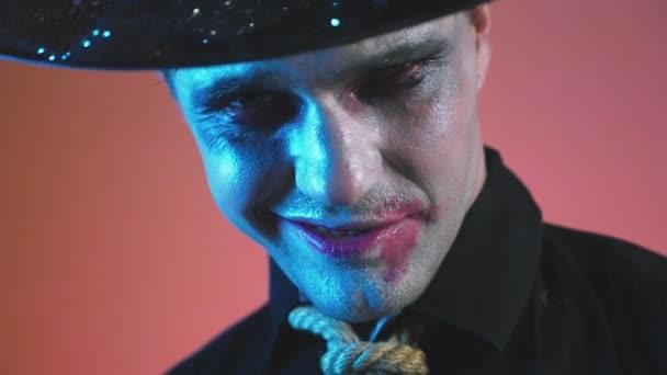ein junger Mann im Zombie-Halloween-Kostüm, blickt in die Kamera und lächelt bedrohlich. 4k, Zeitlupe.