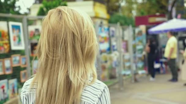 die Frau sieht auf den Bildern, vorbei an dem Stand mit den Bildern, entlang der Fußgängerzone. 4k, Zeitlupe