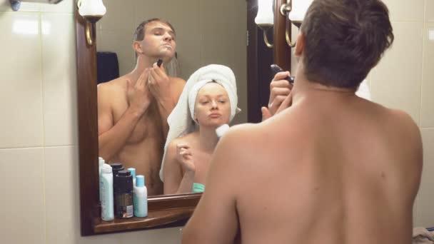 krásný pár, muž a žena, prát spolu prádlo v koupelně před zrcadlem. 4k, Zpomalený pohyb, jeho tvář s obráběcích, Žena je epilace vlasy na její manžel holí