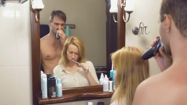 krásný pár, muž a žena, prát spolu prádlo v koupelně před zrcadlem. 4k, Zpomalený pohyb, Žena je čištění zubů, holení muže