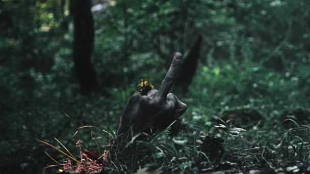Zombiearm klettert aus dem Boden. Zeigt Mittelfinger nach oben