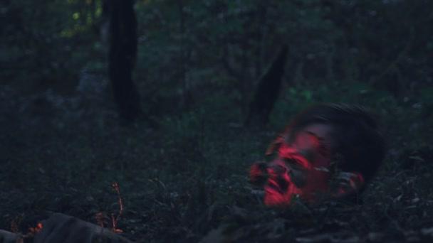 Zombie erhebt sich im Wald aus dem Boden