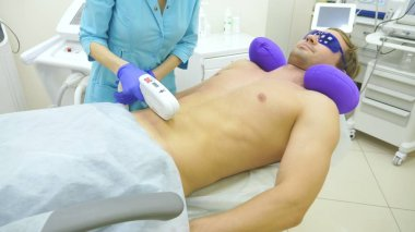 male laser hair removal. a doctor in gloves removes hair from the abdomen and breasts of a man. close-up.