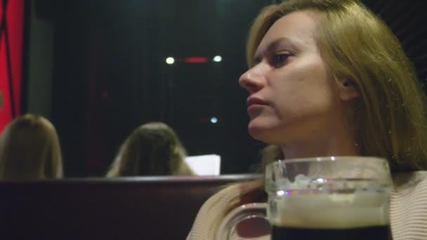 Donna che beve birra scura fresco da un vetro in un locale notturno