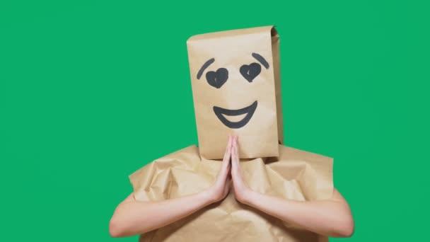 pojmu emoce, gesta. muž s papírové sáčky na hlavě, s malovanými emotikonu, úsměv, radost, láska oči