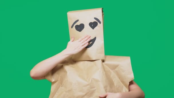concept of emotions, gestures. a man with paper bags on his head, with a painted emoticon, smile, joy, love eyes.