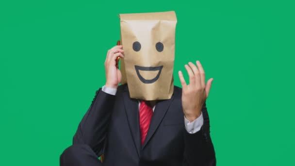 pojmu emoce, gesta. muž s papírové sáčky na hlavě, s malovanými emotikonu, úsměv, radost. mluví o mobilní telefon