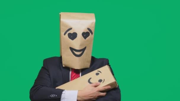 pojmu emoce, gesta. muž s balíčkem na hlavě, s malovanými emotikonu, úsměv, porcelánová panenka oči. hraje si s dítětem malované na box.