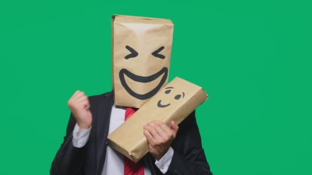 concept of emotions, gestures. man with a package on his head, with a painted emoticon, smile, joy, laughter. plays with the child painted on the box.