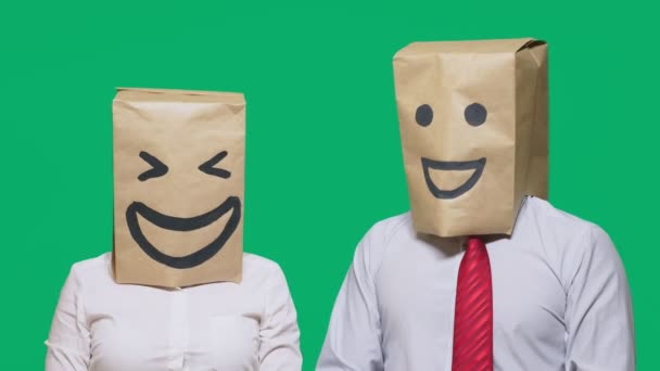 concept of emotions, gestures. a couple of people with bags on their heads, with a painted emoticon, smile, joy, laugh.