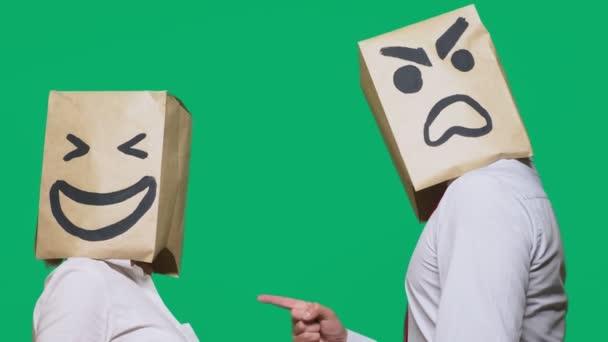 Pojem emoce a gesta. Dva lidé v papírových taškách s úsměvem. Přísahá, že agresivní smajlík. Druhý směje se na něj